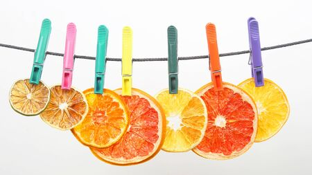 dried pieces of citrus fruits hang on clothespins. healthy and vitamin food