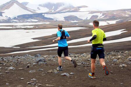 Two athlete runners run a mountain marathon in the snowy terrain of Landmannalaugar. Iceland
