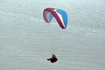 Paraglider flying over the sea Фото со стока