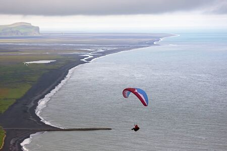 Paraglider flying over the sea Stock Photo