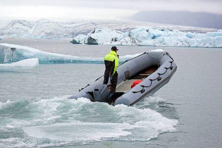 Uomo su una veloce barca a motore che naviga su una laguna glaciale in Islanda