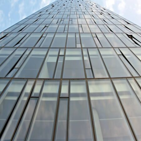 Glass facade of a modern multi-storey building against the sky