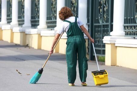 janitor cleans the sidewalk of the city from fallen leaves. work in the field of street cleaning
