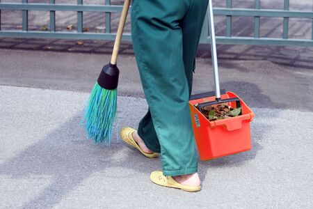 the janitor swept the city sidewalk from the fallen leaves. work in the field of street cleaning Reklamní fotografie