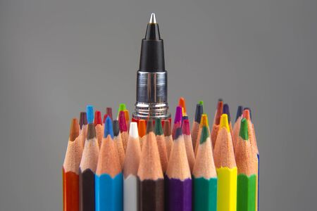 Colored pencils and pen for drawing on a gray background. Education and creativity. Leisure and art Reklamní fotografie