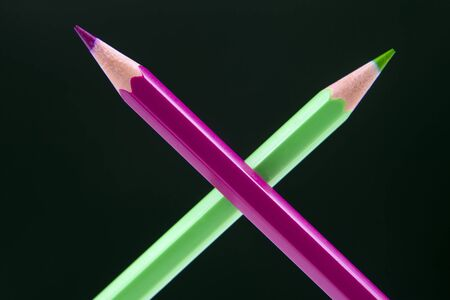 Green and pink pencils for drawing on a dark background. Education and creativity. Leisure and art Reklamní fotografie - 131987251