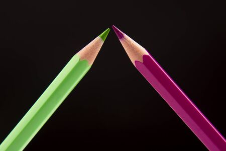 Green and pink pencils for drawing on a dark background. Education and creativity. Leisure and art Reklamní fotografie - 131987506