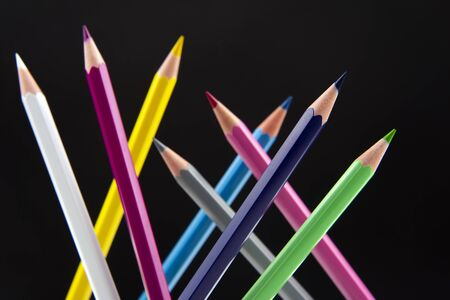 Colored pencils on a dark background. Education and creativity. Leisure and art