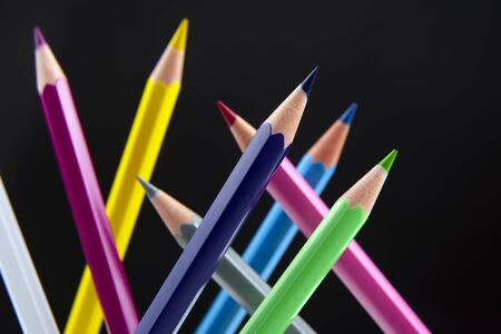 Colored pencils on a dark background. Education and creativity. Leisure and art Reklamní fotografie - 131987493