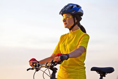 Beautiful girl in a yellow cyclist on a bike reaches in sunlight. Sports and recreation. Nature and man
