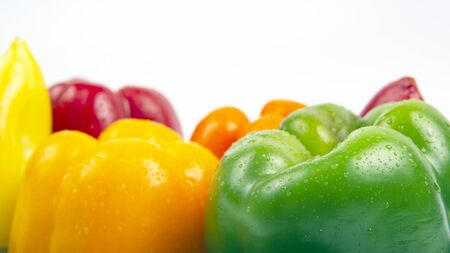 Fresh colored bell peppers on a white background. Vitamin wholesome food.