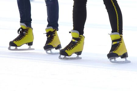 feet in red skates on an ice rink. Sport and entertainment. Rest and winter holidays.