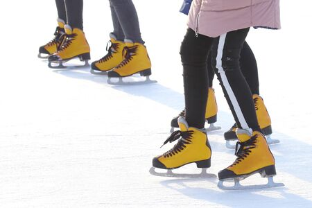 Feet of people skating on a street ice rink. Sport and entertainment. Rest and winter holidays.  版權商用圖片