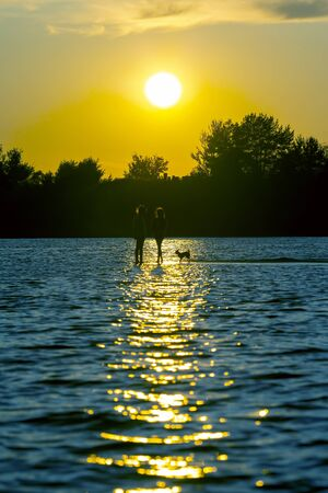 two silhouettes of a child and a dog in the reflection of water on a sunset background. childrens leisure and vacation. 版權商用圖片