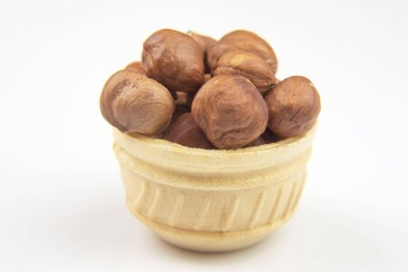 Different nuts in a waffle basket on a white background. Vitamin wholesome food.
