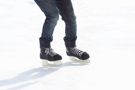 legs ride a guy skating on the ice rink. Sport and entertainment. Rest and winter holidays.