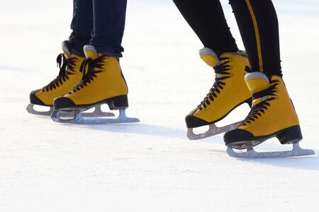 Female legs in skates on an ice rink. Sport and entertainment. Rest and winter holidays.  版權商用圖片