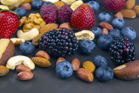 different berries and nuts on a plate. vitamin proteins and healthy foods