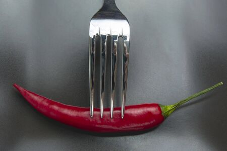 red hot pepper on a fork on a ceramic plate. spices and vegetative food