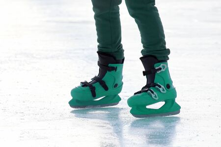 legs in blue skating on the ice rink. Sport and entertainment. Rest and winter holidays.