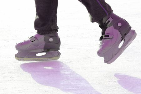Feet skating on the ice rink. Sport and entertainment. Rest and winter holidays.