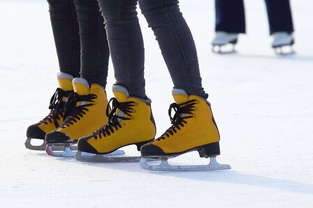 Womens feet skating on the ice rink. Sport and entertainment. Rest and winter holidays.  版權商用圖片