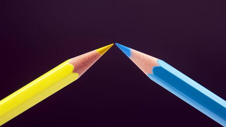 Blue and yellow pencils for drawing on a dark background. Education and creativity. Leisure and art 版權商用圖片