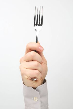 Male hand holds a table fork on a white background  版權商用圖片