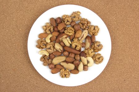 Different kinds of nuts on a white plate. Healthy and protein food