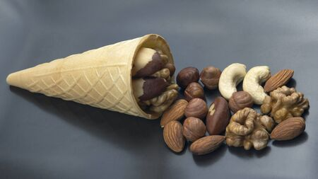 Different types of nuts in a waffle cone on a gray background. Healthy and protein food