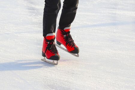 feet in red skates on an ice rink. Sport and entertainment. Rest and winter holidays