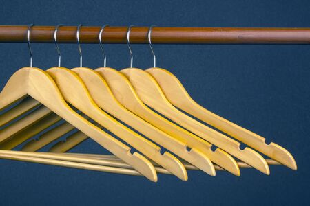 Empty wooden clothes hanger hanging on a dark background. Accessories and items for storing clothes.