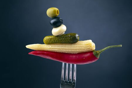 Olives, pickled cucumber, red hot peppers, mushrooms and corn on a fork close-up on a dark background. food and vegetables