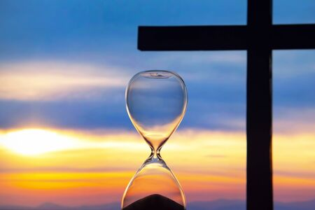 Hourglass has finished counting time on the background of the sunset and a wooden cross. End of life. The value of time in life.