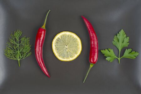 Fresh red hot peppers and lemon on a plate. Vitamin wholesome food. Reklamní fotografie