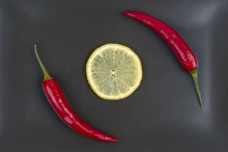 Red hot pepper with lemon on a gray plate. Healthy vegetable food and vitamins Reklamní fotografie