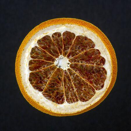dried grapefruit slice on a dark background Reklamní fotografie