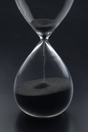 Hourglass on a dark background. Time is money. Business solutions in time. Reklamní fotografie