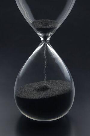 Klepsydra na ciemnym tle. Czas to pieniądz. Rozwiązania biznesowe na czas. Zdjęcie Seryjne