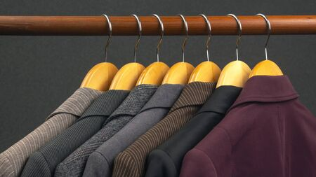 Different women's office classic jackets hang on a hanger for storing clothes. The choice of style of fashionable clothes. 免版税图像