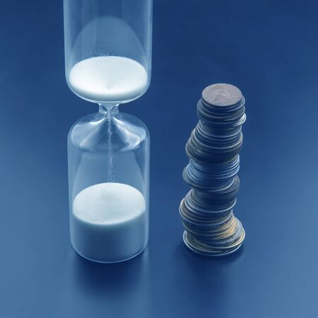 Hourglass with white sand and coins on a dark background. Time is money. Business items. Reklamní fotografie