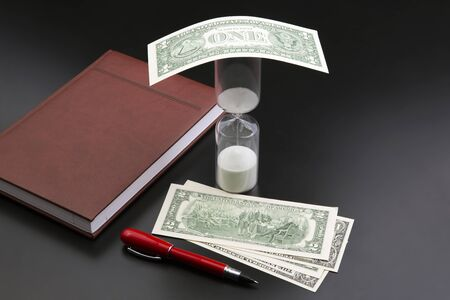 Hourglass, money, pen and notebook are on the table. Business office items. Time is money. Business solutions in time.