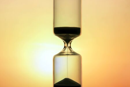 Hourglass on the background of a sunset. The value of time in life. An eternity.