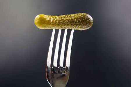 pickled cucumber on a fork on a dark background. food and vegetables