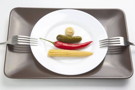 salad of canned and pickled mushrooms, corn, cucumber and red pepper on a white plate.  food and vegetables. diet and weight loss