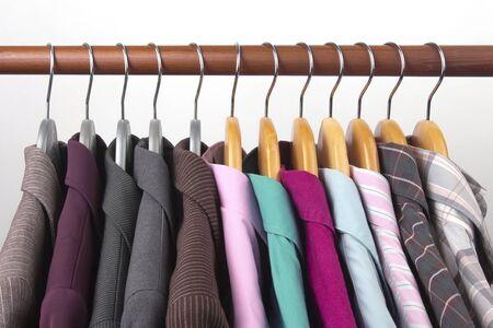 Verschillende klassieke kantoorjassen en overhemden voor dames hangen aan een hanger voor het opbergen van kleding. De keuze van de stijl van modieuze kleding