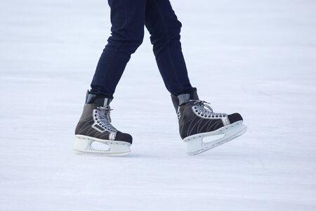 Benen van een man die schaatst op een ijsbaan. Hobby's en sporten. Vakanties en winteractiviteiten