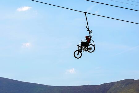 mountain biker climbs on the cable car
