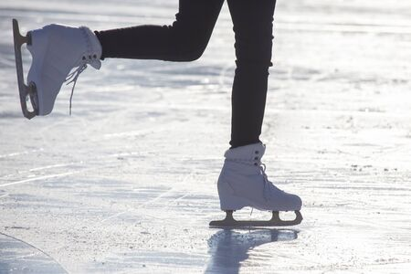 Female legs in white skates on an ice rink. Sport and hobbies. Holidays and winter fun Banque d'images