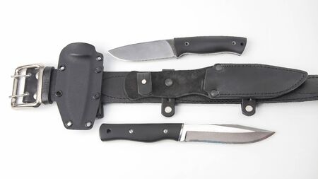knives for tourism and hunting with plastic and leather scabbard on a black leather belt on a white background